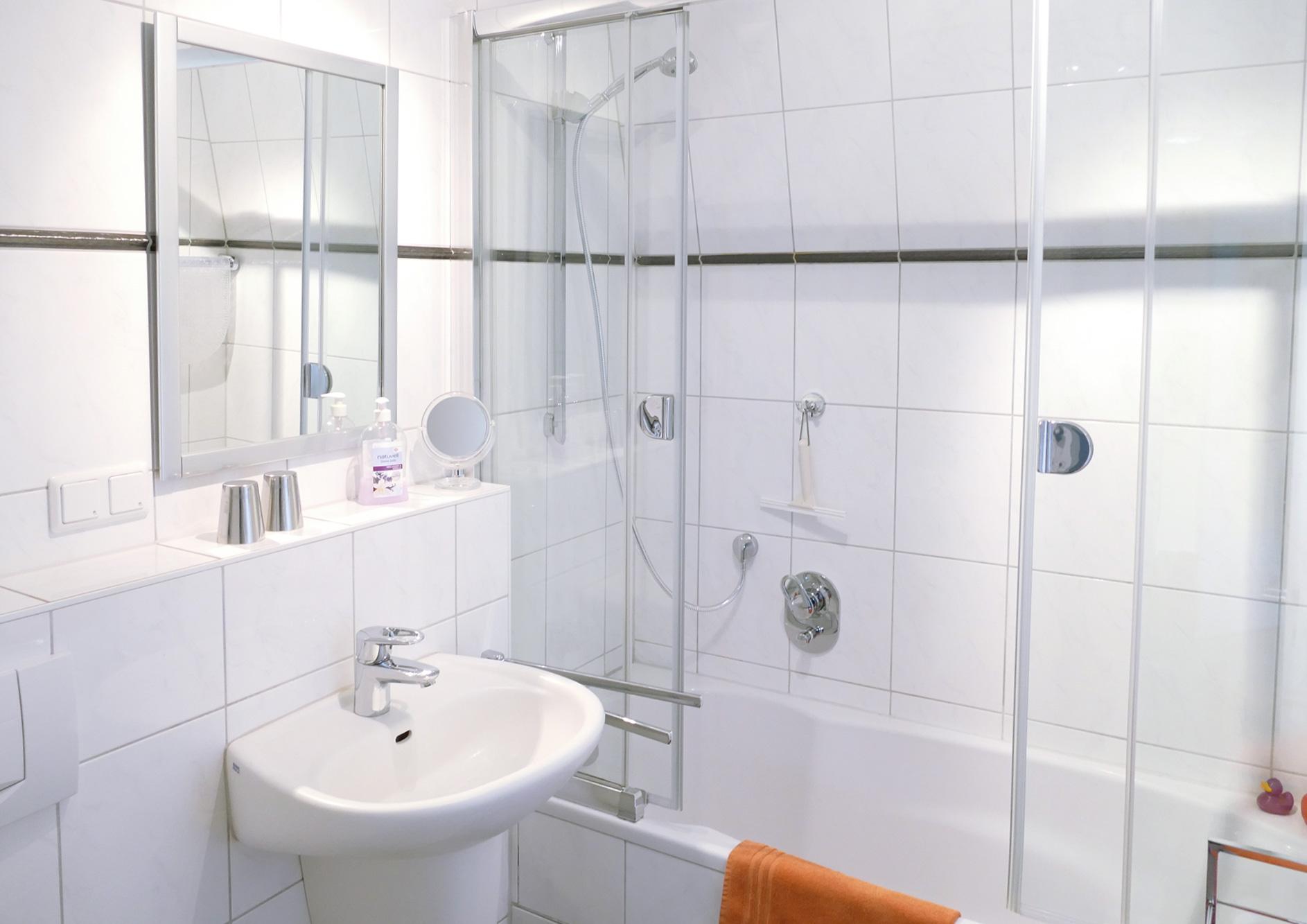 Badezimmer mit Duschbad, Waschbecken und Spiegel
